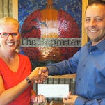 Tammy Young, executive director of Big Brothers Big Sisters, receives a grant check from Jason Kramer, of Action Reporter Media.