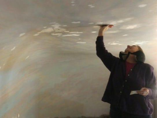 Mary Mullard works on the diorama sky, first sanding