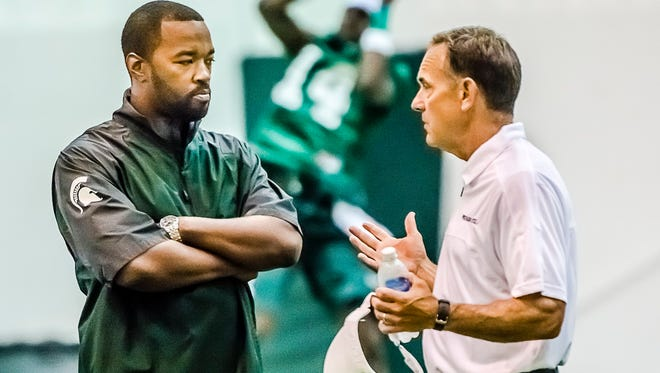 Michigan State director of college advancement and performance/camp director Curtis Blackwell, left, speaks with Mark Dantonio during practice Aug. 3, 2013, at the Duffy Daugherty Building in East Lansing.