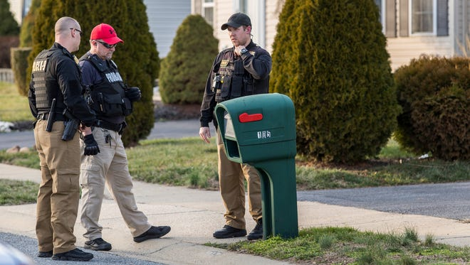Officers stand near a mailbox outside a house at 105 Covington Place in New Castle after a shooting was reported there on Wednesday afternoon.
