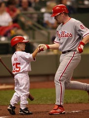 A young Daulton Varsho greets Phillies starter Randy Wolf after Wolf hit a solo home run vs. the Brewers in a 2002 game at Miller Park. Varsho's father, Gary, was a coach for the Phillies at the time.
