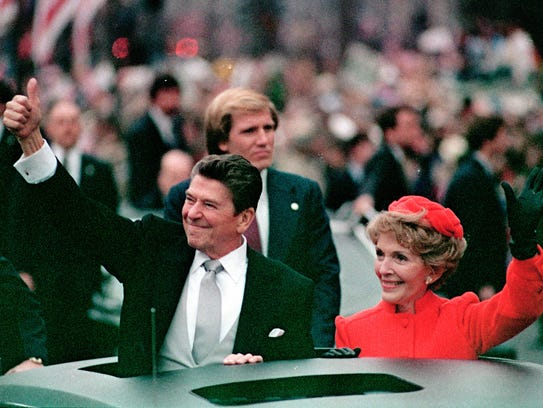 The Reagans wave from a limousine during the inaugural