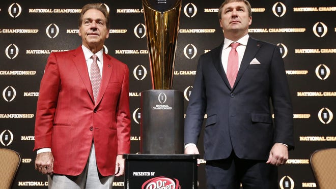 Alabama coach Nick Saban and Georgia coach Kirby Smart have a photo taken with the championship trophy during the coaches press conference in Atlanta Sunday, Jan. 7, 2018.