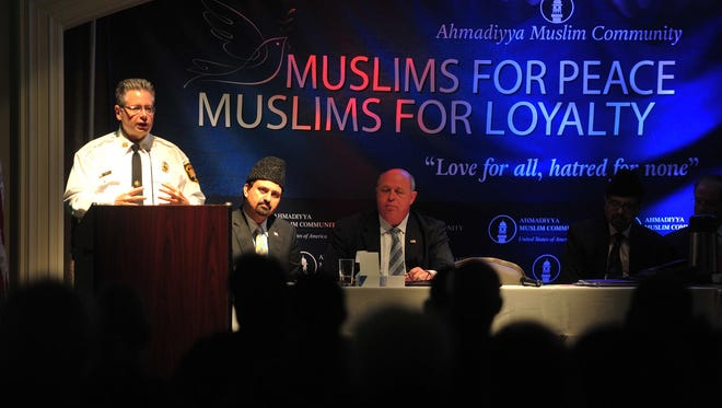 Undersherrif William Schievella speaks at the event. At right are Samiullah Chaudhry, president of the Northern New Jersey Ahmadiyya Muslim Community Chapter and Parsippany Mayor James Barbario.