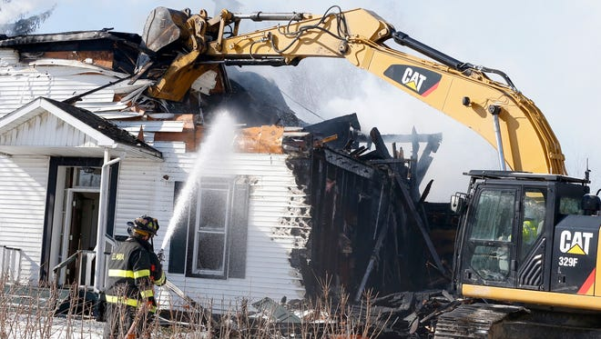 An excavator rips out a portion of the outer wall of the house at 326 West Ave. on Elmira's Southside Tuesday, hours after an early morning structure fire ripped through the two-unit home.