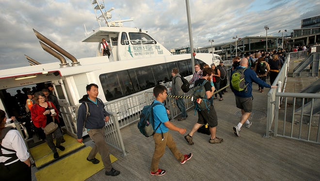Passengers from 6:15 AM departure from Seattle disembark the Rich Passage 1 at the Bremerton dock on Monday, July 10, 2017.