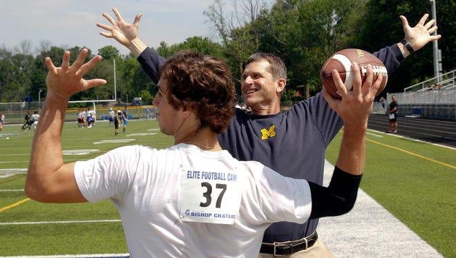 Michigan coach Jim Harbaugh works with Brandon Peters during a camp in Indianapolis in June.