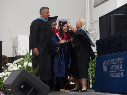 St. Lucie County School District superintendent E. Wayne Gent (left) and St. Lucie West Centennial High School exceptional student education teacher Tracy Hogan (right) help graduate Janeli Inglesacross the stage during the 2017 commencement ceremony at the Havert L. Fenn Center in Fort Pierce. The district is one of nine county school districts to challenge a controversial charter school law.