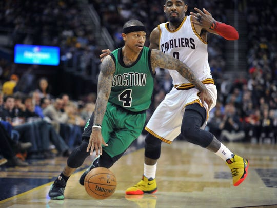 Former Boston Celtics guard Isaiah Thomas dribbles past former Cleveland Cavaliers guard Kyrie Irving.