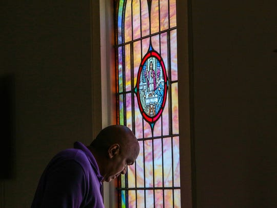 The Rev. Edgar Scott looks at an older church Bible near a window in the dining hall, converted from a previous sanctuary in 2001, at Generostee Baptist Church in Starr.