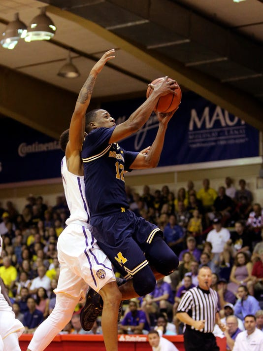 LSU guard Brandon Sampson, left, can't stop Michigan guard Muhammad-Ali Abdur-Rahkman, right, from flying towards the bucket during the first half of an NCAA college basketball game, Monday, Nov. 20, 2017, in Lahaina, Hawaii. (AP Photo/Marco Garcia)