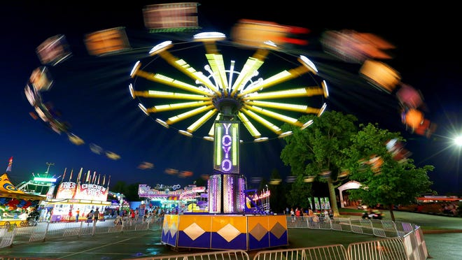 The Yoyo swing ride flies into the night on the midway at the Indiana State Fair on Monday, August 10, 2015.