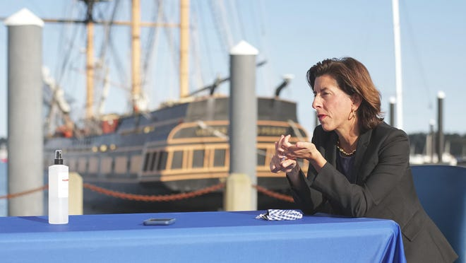 The Oliver Hazard Perry is docked in the background at Fort Adams State Park as Gov. Gina Raimondo talks to a reporter about two programs to help people and businesses in Newport County recover from the coronavirus pandemic.