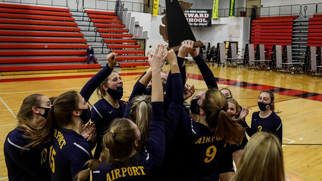 Airport's volleyball team celebrates with the District Trophy Thursday night after defeating Milan.