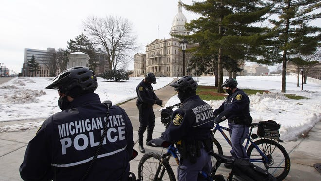 Michigan State Police officers patrol around the Michigan State Capitol building in Lansing on Wednesday, January 13, 2021 before the Michigan State Legislature House and Senate sessions begin.