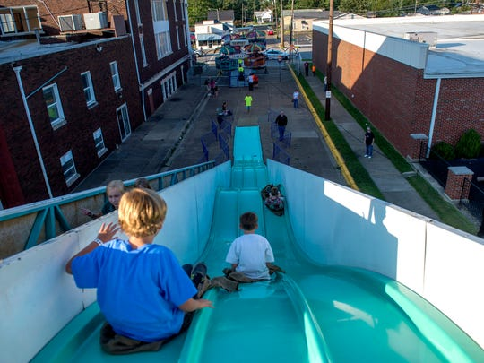Children go down the slide during the Holy Name Fall Festival at Holy Name Elementary School in Henderson, Ky., on Friday, Sept. 8, 2017.