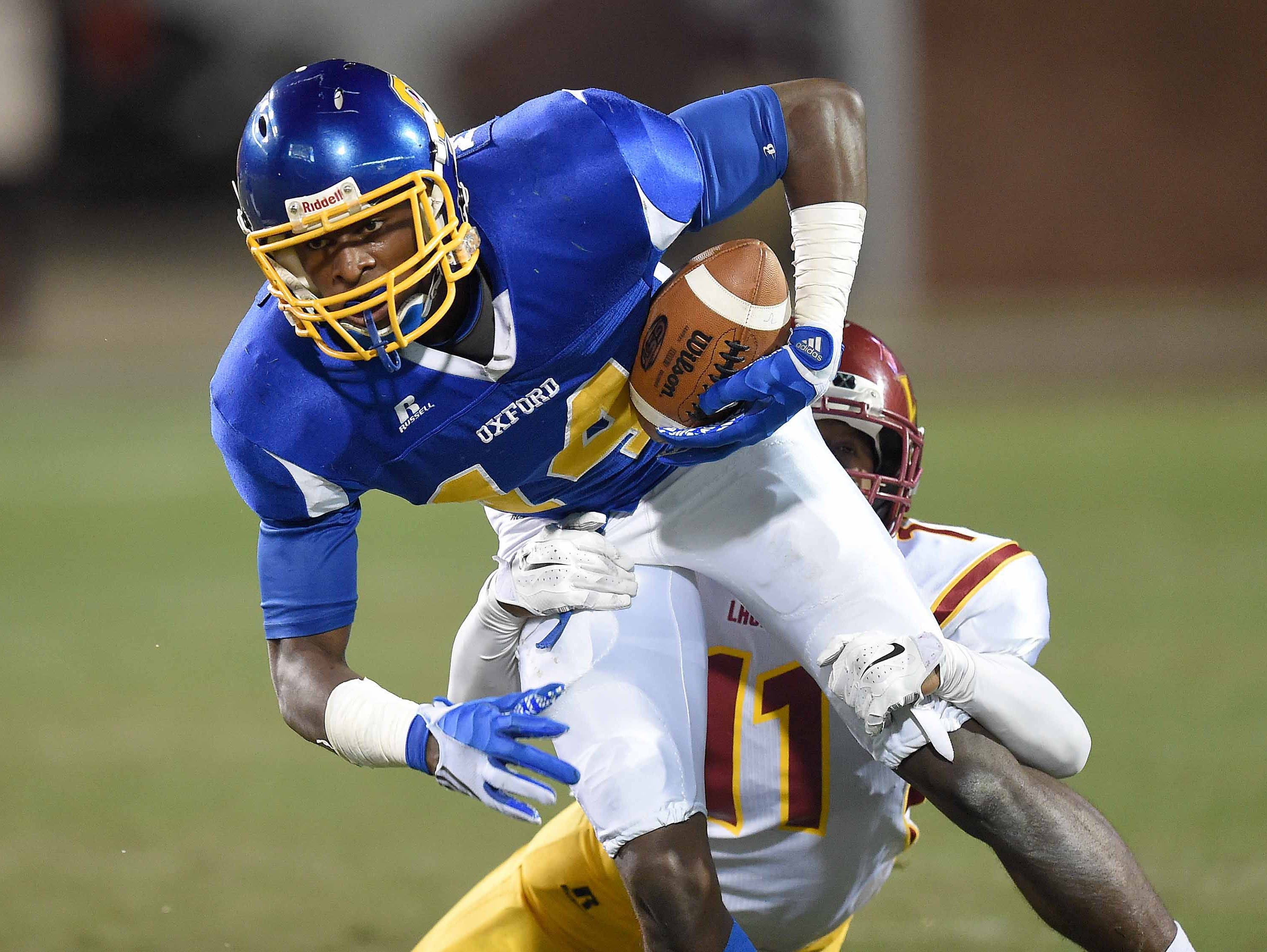 Oxford wide receiver Dekaylin Metcalf tries to break free from Laurel's Shemar Keyes in the MHSAA football state championships on Saturday, December 6, 2014, at Davis Wade Stadium on the Mississippi State University campus in Starkville.