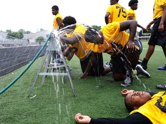 Members of King High School's football team cool off after running drills during practice.