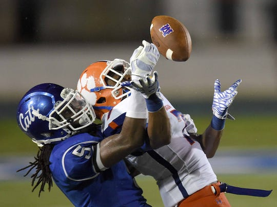 Madison Central's Quentin Euell (7) juggles the ball before making the reception against Meridian's Zaire Jone (5) on Friday, August 21, 2015, at Meridian High School in Meridian, Miss.