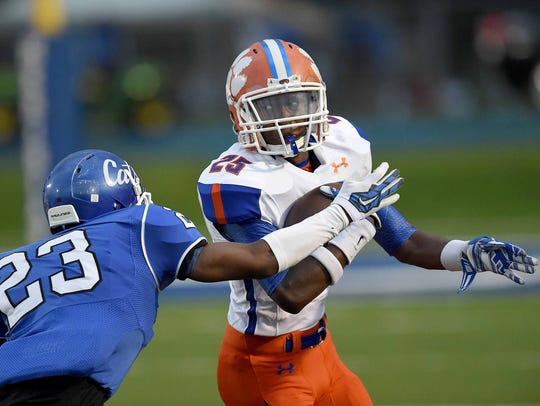 Madison Central's Cam White (25) tries to get by Meridian's