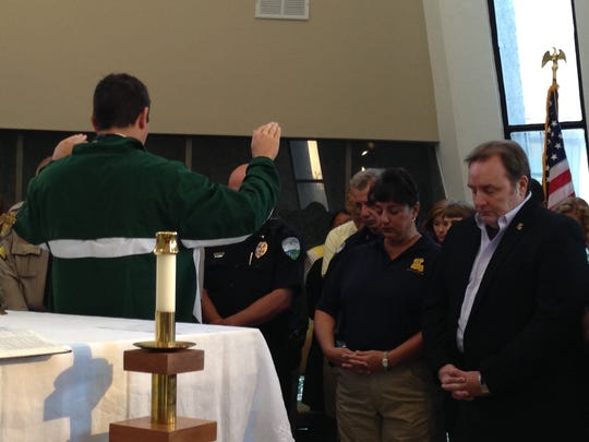 Father Taylor Reynolds blesses law enforcement officers Monday during a chapel service at Holy Savior Menard Central High School.