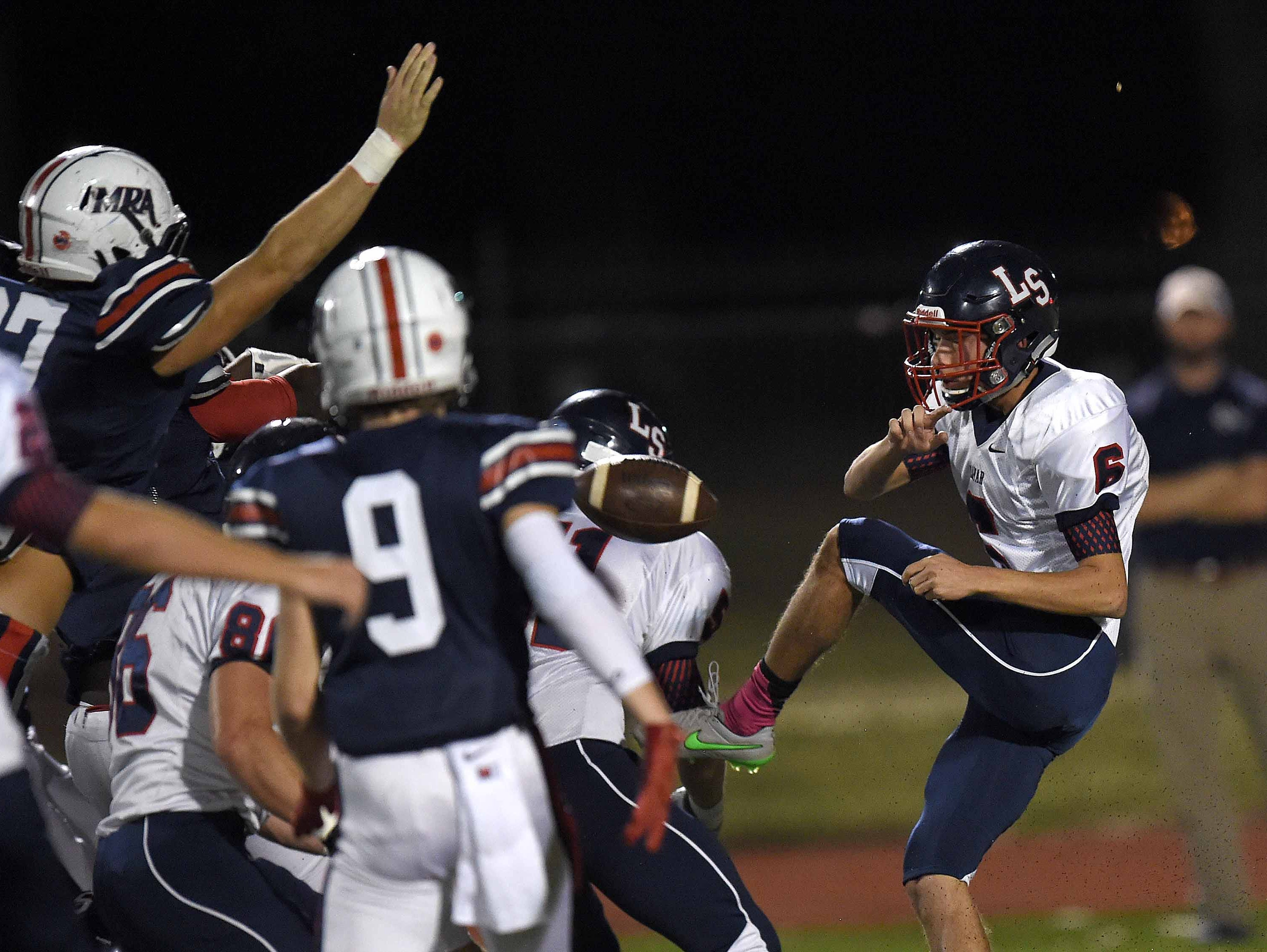 MRA's Lilewis Davis (far left, hand raised) blocks the punt by Lamar's Zack Engell (6) on Friday, October 30, 2015, at Madison-Ridgeland Academy in Madison, Miss. The recovered punt led to MRA's first touchdown.