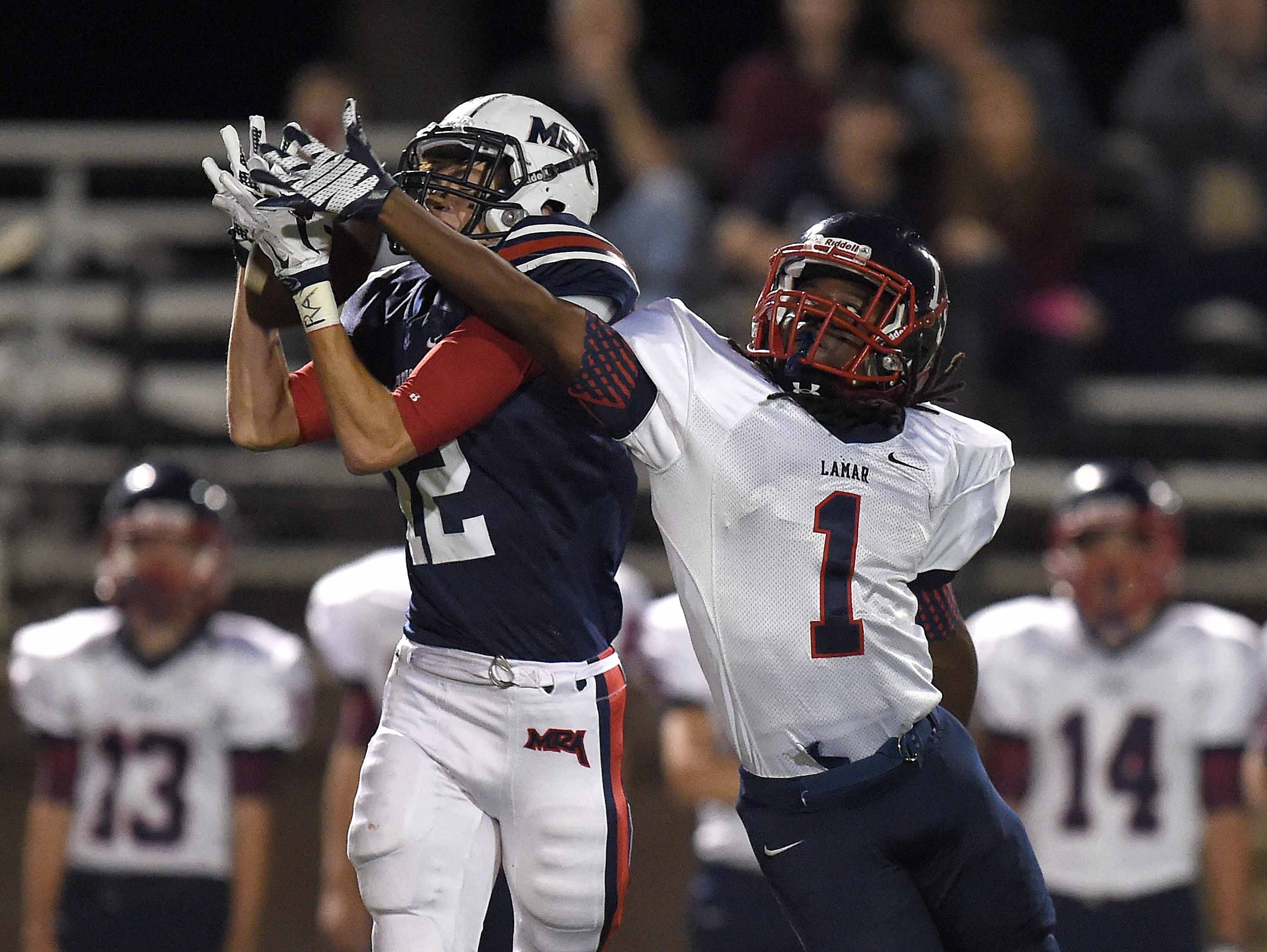 MRA's Kory Stephens (12) makes a catch against Lamar's J.T. McClelland (1) on Friday, October 30, 2015, at Madison-Ridgeland Academy in Madison, Miss.