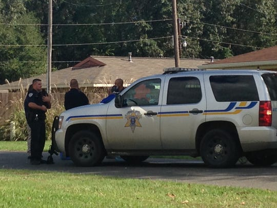 Police officers stand near an Avoyelles Parish Sheriff's Office unit during a standoff on Wednesday.