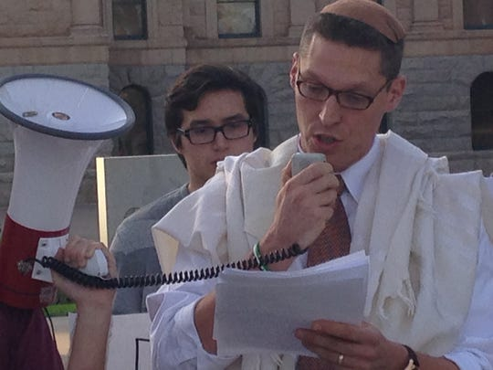 Rabbi Dr. Shmuly Yanklowitz speaks during a protest
