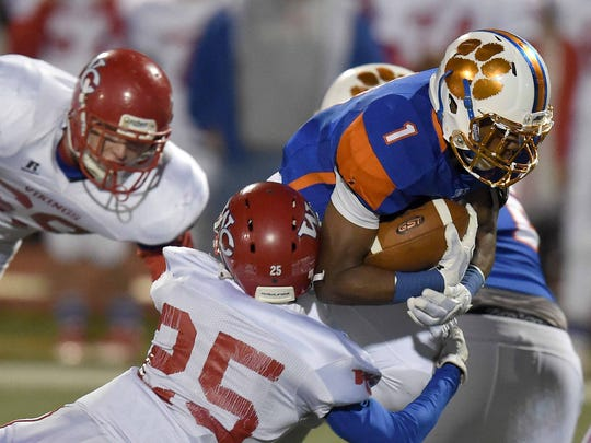 Madison Central's Jaylon Uzodinma (1) is tackled by Warren Central's Cedric Harris (25) on Friday, November 20, 2015, at Madison Central High School in Madison, Miss.