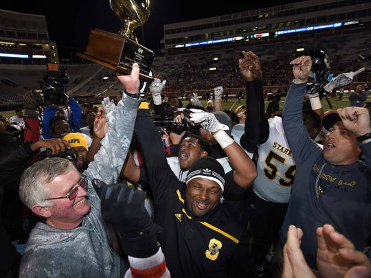 The Starkville Yellowjackets and head coach Ricky Woods (left) celebrate with the trophy after beating Petal 27-7 on Friday, December 4, 2015, at the MHSAA Class 2A State Football Championships in Vaught-Hemmingway Stadum on the Ole Miss Campus in Oxford, Miss.