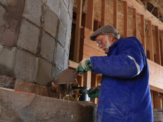 John Cramner, a stonemason for Lillywhite Stone, applies mortar to a C. Blake Homes project in The Ledges development of St. George.