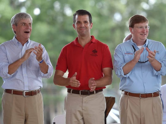 Gov. Phil Bryant (left), Donald Trump Jr. (center) and Lt. Gov. Tate Reeves applaud the large crowd from the stage at the racetrack on the Neshoba County Fairgrounds on Tuesday, July 26, 2016.