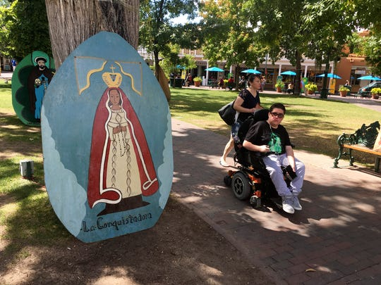 This Sept. 1, 2016 photo shows visitors of Santa Fe Plaza pass by an image of La Conquistadora, oldest statue of the Blessed Virgin Mary in the United States, as organizers prepare for the annual Santa Fe Fiesta.  For centuries, northern New Mexico Hispanic residents have held an elaborate festival in Santa Fe in honor of Spanish conquistador Don Diego De Vargas' who reclaimed the city following an American Indian revolt.  But after 301 years, an emboldened group of Native American activists say it's time to change a celebration centered around the conquest of New Mexico's Pueblo tribes.