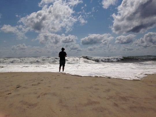 A beachgoer stands at the edge of the water, Sunday, Sept. 4, 2016, in Bridgehampton, N.Y., on the southeastern shore of Long Island, where the effects of storm system Hermine could be seen in the rough surf and a ban on swimming. Hermine spun away from the U.S. East Coast on Sunday, removing the threat of heavy rain but maintaining enough power to churn dangerous waves and currents and keep beaches off-limits to disappointed swimmers and surfers during the holiday weekend.