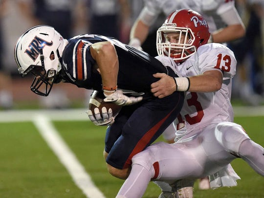 Prep's Maddox Henry (13) hangs on to MRA receiver Lee