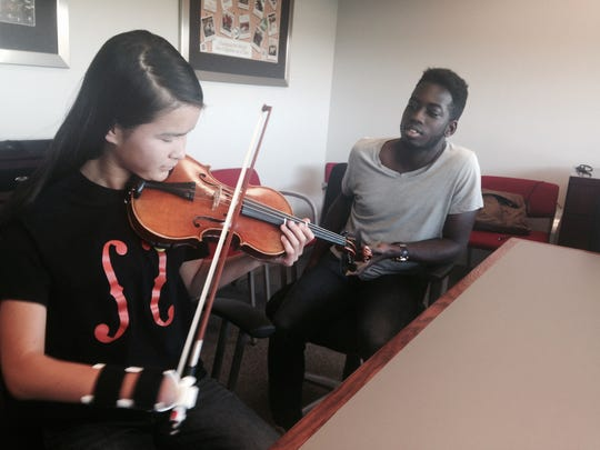 Sarah Valentiner of DeKalb plays her violin using the prosthetic designed by Northern Illinois University engineering student, Oleseun Taiwo, of Naperville on September 26, 2016. (Denise Crosby/Chicago Tribune/TNS)