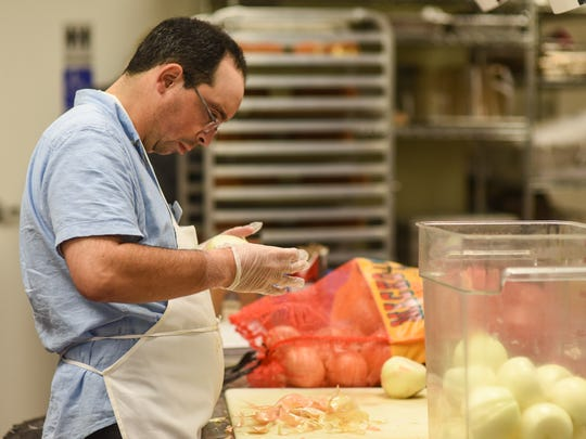 Ben Nadis peels onions in the kitchen at Soul Cafe in West Bloomfield.