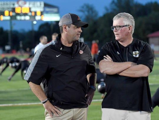 Clinton head coach Judd Boswell (left) talks with Starkville