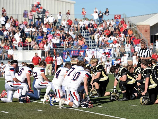 Tri-County and Canton Academy players kneel on the first play of the game to honor Rebels center Taylor Martin who died in a car accident two days before the MAIS A-AA championship game.