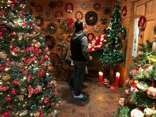 A visitor looks at wreaths at the History of the Christmas