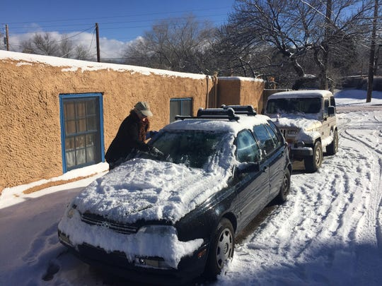 Peggy Blitz, 76, of Santa Fe, N.M., clears her windshield of ice as residents dig out from a winter storm that closed schools and blanketed nearby ski resorts with snow on Friday, Jan. 6, 2017. Authorities reported difficult driving conditions on on the state's two main interstate highways. (AP Photo/Morgan Lee)