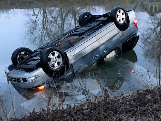 A woman was rescued after her car jumped a curb and landed upside down in the Central Canal Towpath in Broad Ripple, Wednesday, Jan. 11, 2017.