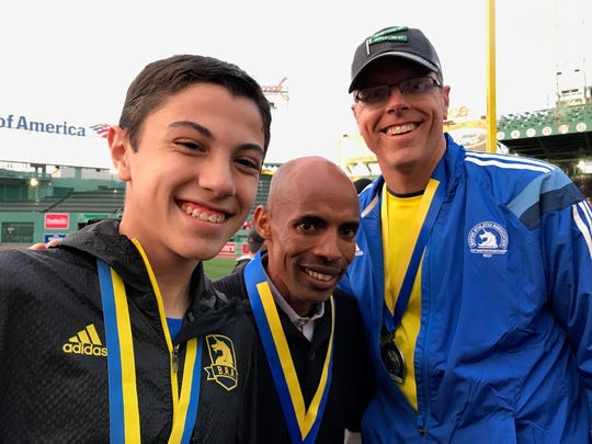 Daryl Crum, right, the Adams County director of tax services, poses with his son Kalani Crum, left, and U.S. Olympian Meb Keflezighi, center, at the Boston Marathon on Monday, April 17, 2017.