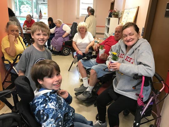 Isaac and Lucas Keepfer (left-right) of Silver Run Elementary School talk with some residents of Riverview West high-rise during a delivery of potted flowers on Monday morning.