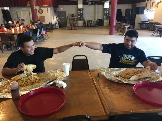 Christopher Villarreal(left) and Cristian Lopez(right) giving each other first bump after trying to complete the Recio's Breakfast Taco Challenge