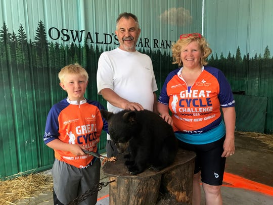 Zack Helminen, 10, feeds a black bear cub at Oswald's