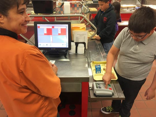 Cafeteria worker Paula Herrera, left, supervises as second grade student Dylan Casias punches in his student identification number to deduct a meal payment at Gonzales Community School in Santa Fe, N.M.