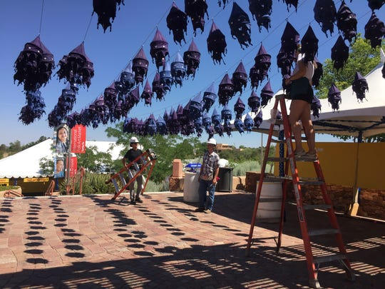 This July 10, 2017 photo workers hang lantern decorations at the entrance to the International Folk Art Market in Santa Fe, N.M. Organizers of the market say shifting U.S. policies on security and immigration have not hampered participation by artists from 53 countries, from Cuba to Jordan. In its 14th year, the annual bazaar is expanding its mission to highlight innovation and high-fashion within folk art traditions.