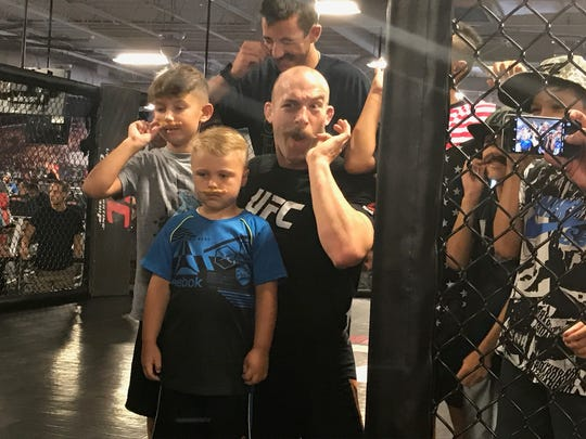 Patrick Cummins teaches children how to twirl their fake mustaches during open workouts Thursday for UFC Fight Night: Long Island. Cummins -- and his quite-real mustache --  fights Gian Villante on Saturday in Long Island.